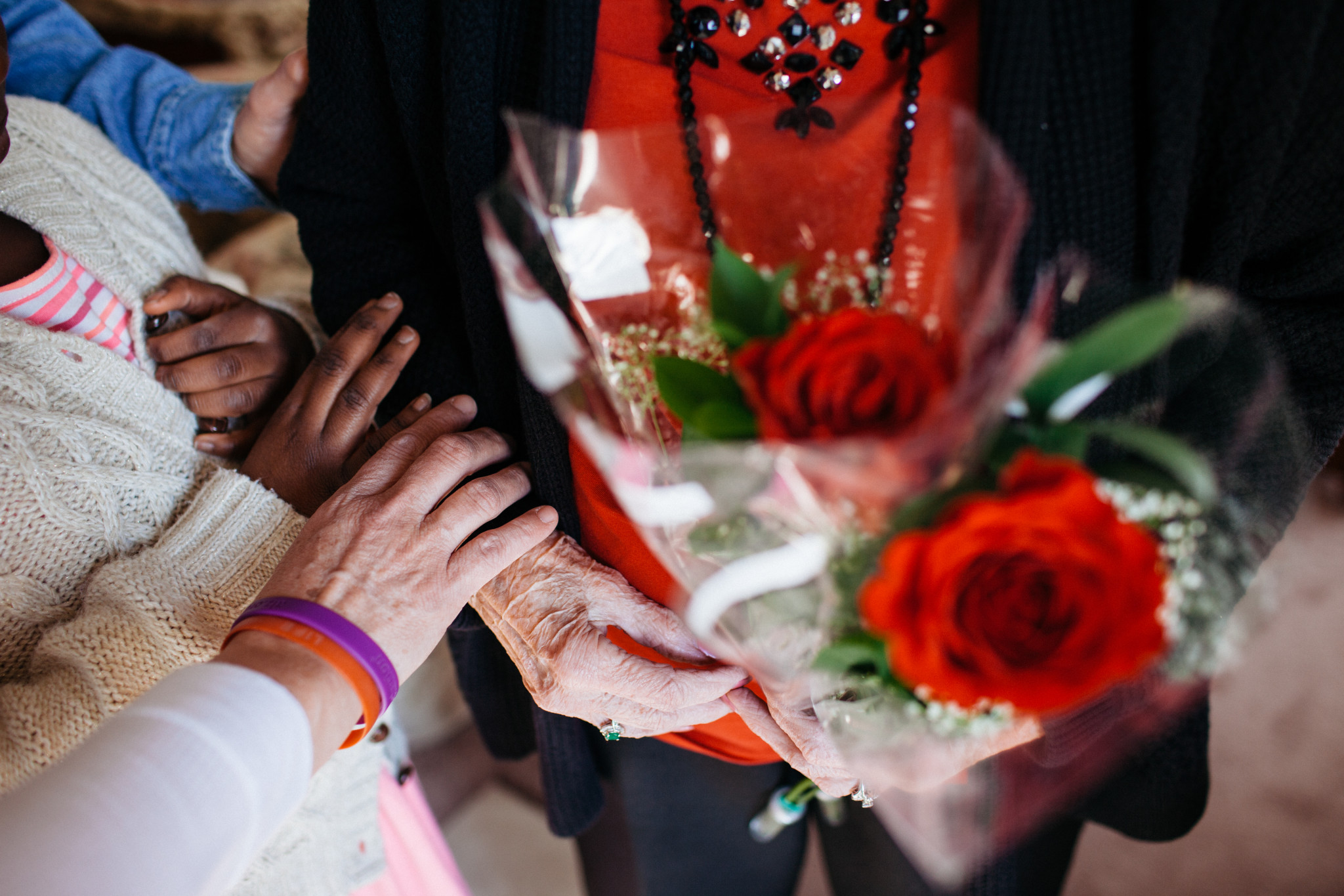 Volunteers pray with a local widow after delivering roses for Valentine's Day 2016.
